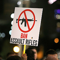 A sign calling to ban assault rifles is seen in the crowd during a vigil at the Dr. Phillips Center for the Performing Arts for the victims of a mass shooting at the Pulse nightclub Monday, June 13, 2016, in Orlando, Florida.  A gunman killed dozens of people in a massacre at the crowded gay nightclub in Orlando on Sunday, making it the deadliest mass shooting in modern U.S. history. (Alex Menendez via AP)