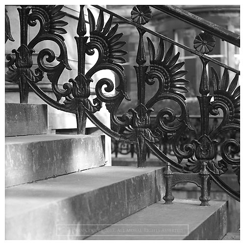 Black and white photograph of ornate cast iron railings and boot scraper at terraced house in the West End of Glasgow. Designed by Alexander 'Greek' Thomson and produced at the Saracen Foundary, Glasgow. Mounted print available to purchase.