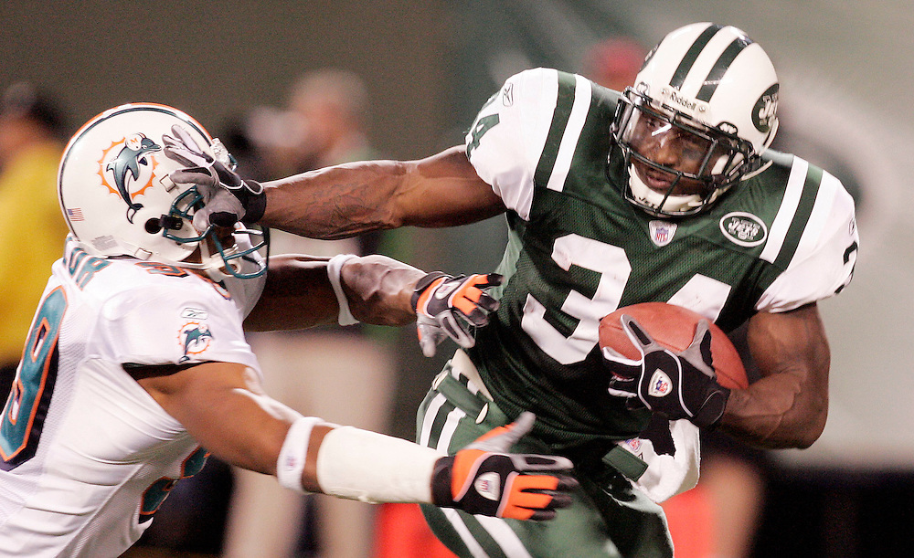 New York Jets running back LaMont Jordan (R) tries to avoid being tackled by the Miami Dolphins defensive end Jason Taylor (L) during the fouth quarter of their game at Giants Stadium in East Rutherford New Jersey Monday 01 November 2004.   EPA/ANDREW GOMBERT