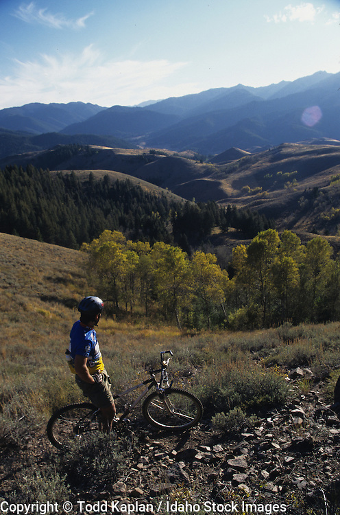 Idaho.  Boulder Mountains.  Mountain biker rides past peaks near Sun Valley on a cloudy day.