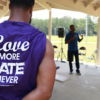 Community Outreach Coordinator Marcus Gary listens to the words of White Hill Baptist Church Pastor Jeffery Daniel while sporting a shirt with the name and message of this community gathering.