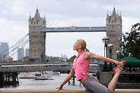 Woman stretching in front of Tower Bridge England London
