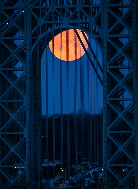 A large moon sets under the George Washington bridge at sunrise in New York City.