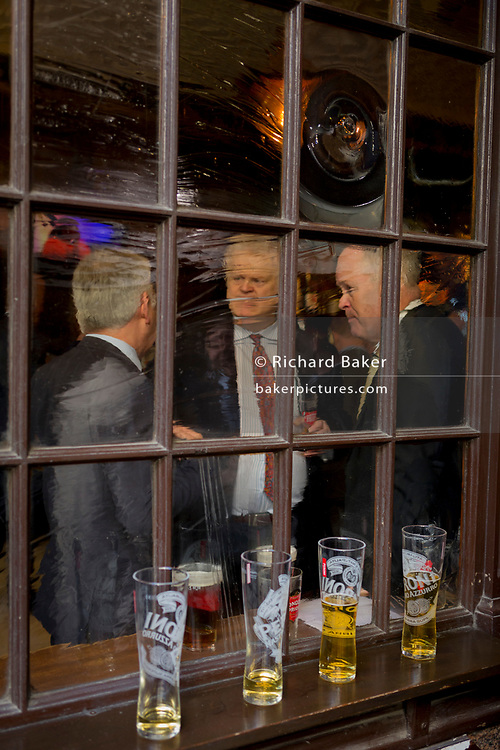 As nearly-empty lager glasses are lined up on a sill of a City on Lime Street, male businessman enjoy after-work drinks, on 10th May 2017, in the City of London, England.