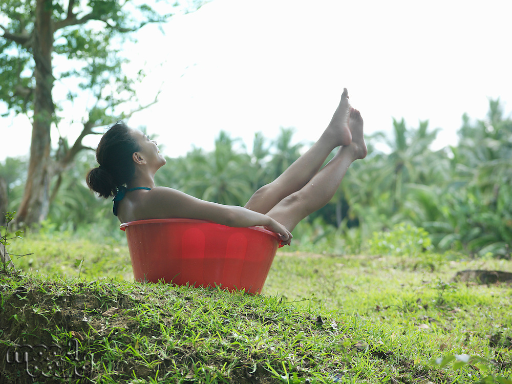 Young woman sitting in bowl outdoors side view