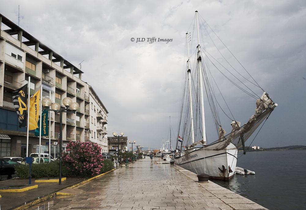 """The schooner """"Flying Dutchman"""" moored at Sribenik harbor.  The Dutch registered ship carries a dozen passengers, captain, crew.  Modern hotel opposite the ship."""