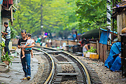 07 APRIL 2012 - HANOI, VIETNAM: A man carries his child along the train tracks in Hanoi, the capital of Vietnam. Hanoi is one of the oldest cities in Southeast Asia. It was established in 1010 A.D.   PHOTO BY JACK KURTZ