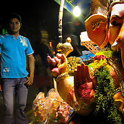 Statue of the Hindu god Ganesh, erected in the marketplace for the Festival of Ganesh, attended to by a nearby shop keeper, Little India, Singapore. Photo by Jen Klewitz