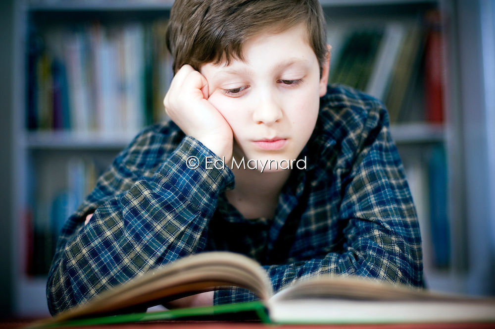 Ten year old boy reading a book, leaning on his elbow, England, United Kingdom.