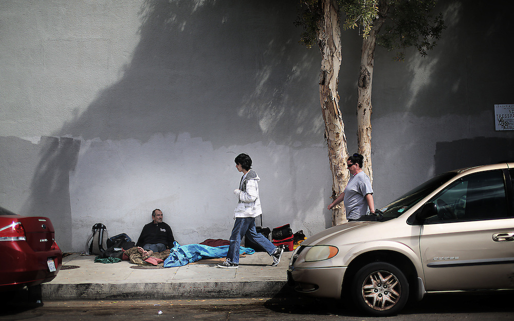 A student from the Monarch School walks past a homeless man with his Mom on the way to his home in San Diego, CA on Monday, May 18, 2015.  The Monarch School is the largest elementary through High School facility that caters to students that are homeless or are have associations with homelessness.(Photo by Sandy Huffaker for The Atlantic)