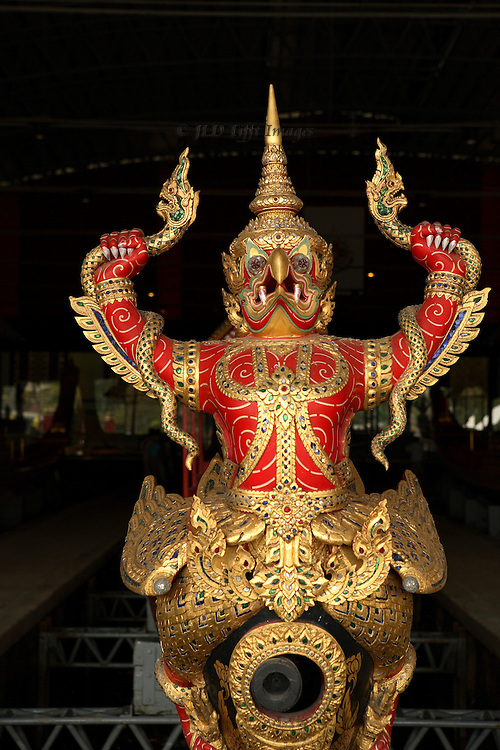 Figure on the prow of one of the Thai royal barges, in the Royal Barge Museum, Bangkok.  Frontal view showing gilded and bejeweled ferocity of the deity represented.