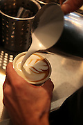 Preparing cappuccino Adding hot milk froth to espresso coffee and creating a four leaf design