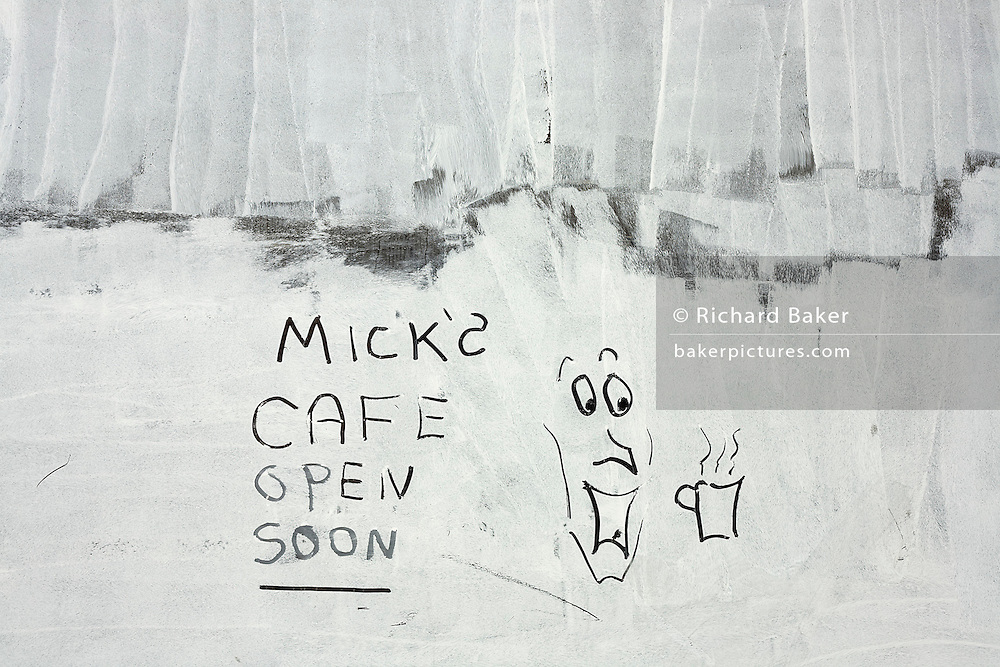 A cartoon picture and re-opening writing have been drawn in white emulsion paint, smeared over a shop window, a victim of the UK recession.