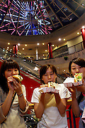 Three girls chow down on A&W hot dogs at Mihama American Village on Okinawa's main island. Okinawa, Japan. The A&W fast food chain is found all around Okinawa's main island, as are soft drink advertisements. (Supporting image from the project Hungry Planet: What the World Eats)