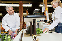 Mid adult chef with shopping cart standing at checkout counter with senior female employee in market
