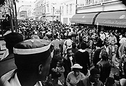 Man in a leather hat watches the crowd in a street below from a large lorry containing a big steel drum band, Notting Hill Carnival, London, 1989