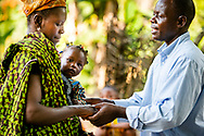 Pastor Nathaniel S. Abu of the Christ Evangelical Lutheran Church—Sierra Leone (CELC—SL), prays with patients following treatment on the first day of the LCMS Mercy Medical Team on Monday, May 7, 2018, in the Yardu village outside Koidu, Sierra Leone, West Africa. LCMS Communications/Erik M. Lunsford