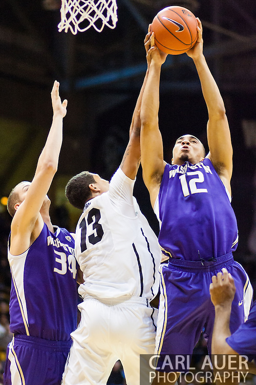 February 9th, 2014:  Washington Huskies sophomore guard Andrew Andrews (12) elevates to grab a rebound away from Colorado Buffaloes freshman forward Dustin Thomas (13) in the second half of the NCAA Basketball game between the Washington Huskies and the University of Colorado Buffaloes at the Coors Events Center in Boulder, Colorado