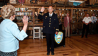 Ann Kaligian swears in Laconia's Chief of Police Christopher A. Adams with Laconia Police Commissioner Armand Maheux and retired Chief Michael Moyer looking on at The Freight Room Tuesday afternoon. (Karen Bobotas/for the Laconia Daily Sun)