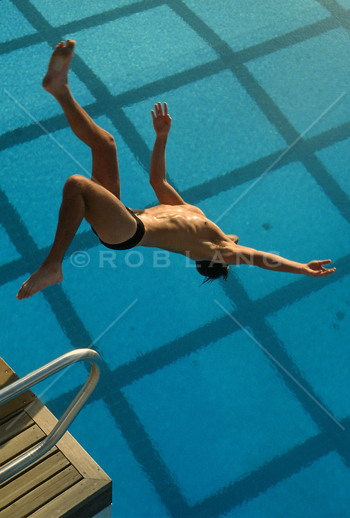 Diver doing a back flip off a high drive into a swimming pool