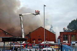 © Licensed to London News Pictures. 07/08/2018. Manchester, UK.  Emergency services at the scene of a fire at a commercial knitwear building on Hyde Road in Ardwick, Manchester.  Over 50 firefighters are tackling the blaze which broke out after a factory caught fire at about 7pm yesterday evening. Photo credit: Terry Waller/LNP