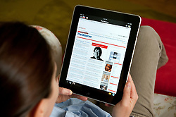 Woman using iPad tablet computer at home to read The Observer UK newspaper