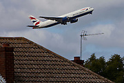 A British Airways Boeing 777 taking off from London Heathrow, south runway close to local houses in Hatton.