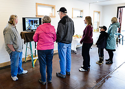Joanne Waterman (left) and visitors watch a slideshow documenting the restoration of the recently restored fire hall located on the grounds of historic Fort William H. Seward in Haines, Alaska during an open house for the fire hall. rounds.<br /> <br /> The fire hall was restored over a two-year period by owners Waterman and Phyllis Sage who also own the fort&rsquo;s original guardhouse, now a bed and breakfast, located next door to the fire hall.<br /> <br /> After being absent from the historic Fort Seward skyline since approximately the 1930s, the 60-foot tower of the fort&rsquo;s fire hall has been restored to its original height. The building and tower, built around 1904 in Haines, Alaska, was shortened to approximately half its height in the 1930s for unknown reasons. The restoration included rebuilding a missing 35-foot section of the 60-foot tower whose purpose was to dry fire hoses. The tower restoration was completed by building its four sections on the ground and then hoisting those sections with a crane into place on top of each other.<br /> <br /> Through the years, the historic Fort Seward area, a former U.S. Army post, has been referred to as Fort William H. Seward, Chilkoot Barracks, and Port Chilkoot. The National Historic Landmarks listing record for the fort says that &quot;Fort Seward was the last of 11 military posts established in Alaska during the territory's gold rushes between 1897 and 1904. Founded for the purpose of preserving law and order among the gold seekers, the fort also provided a U.S. military presence in Alaska during boundary disputes with Canada. The only active military post in Alaska between 1925 and 1940, the fort was closed at the end of World War II.&rdquo; <br /> <br /> The bottom portion of the fire hall is being leased as commercial space. Due to fire code restrictions there is no public access to the upper portion of the tower.
