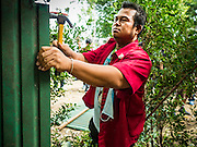03 SEPTEMBER 2016 - BANGKOK, THAILAND:  A Bangkok city worker tears down a fence around the Pom Mahakan Fort. Hundreds of people from the Pom Mahakan community and other communities in Bangkok barricaded themselves in the Pom Mahakan Fort to prevent Bangkok officials from tearing down the homes in the community Saturday. The city had issued eviction notices and said they would reclaim the land in the historic fort from the community. People prevented the city workers from getting into the fort. After negotiations with community leaders, Bangkok officials were allowed to tear down 12 homes that had either been abandoned or whose owners had agreed to move. The remaining 44 families who live in the fort have vowed to stay.     PHOTO BY JACK KURTZ
