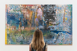 "© Licensed to London News Pictures. 30/05/2019. LONDON, UK. A staff member poses next to ""Towards Crab Island"", 1983, by Frank Bowling at a preview of works by artist Frank Bowling (born in Guyana in 1934).  The retrospective exhibition spans his six-decade career and takes place 31 May to 26 August 2019 at Tate Britain.  Photo credit: Stephen Chung/LNP"
