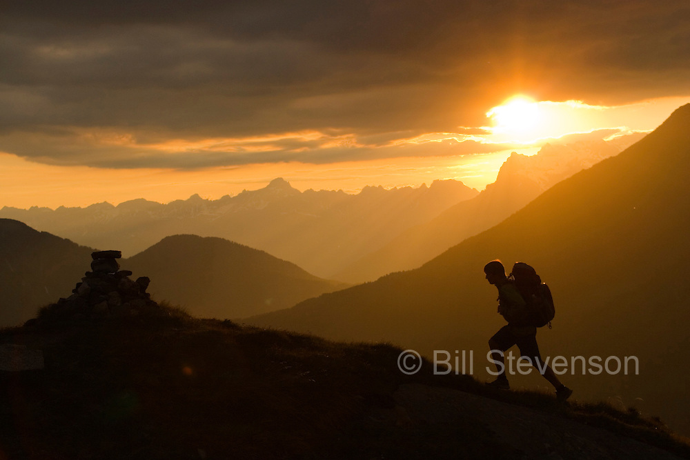 A photo of a man hiking in the French Alps near Chamonix at sunset.