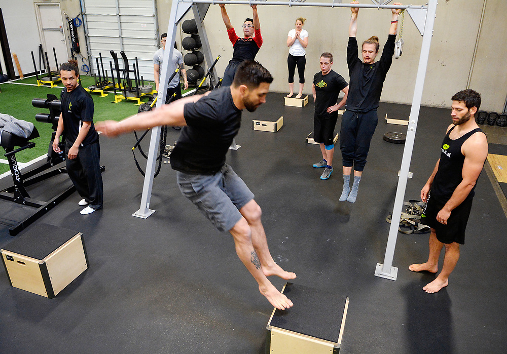 "gbs040217d/GO -- Carlos Condit of Albuquerque jumps between boxes during a MoveNat workshop at Elevate where coaches learn how to incorporate this type of movement ""play"" into strength and conditioning programs. MoveNat is a comprehensive, holistic and mindful approach to the full range of natural human movement abilities. (Greg Sorber/Albuquerque Journal)"