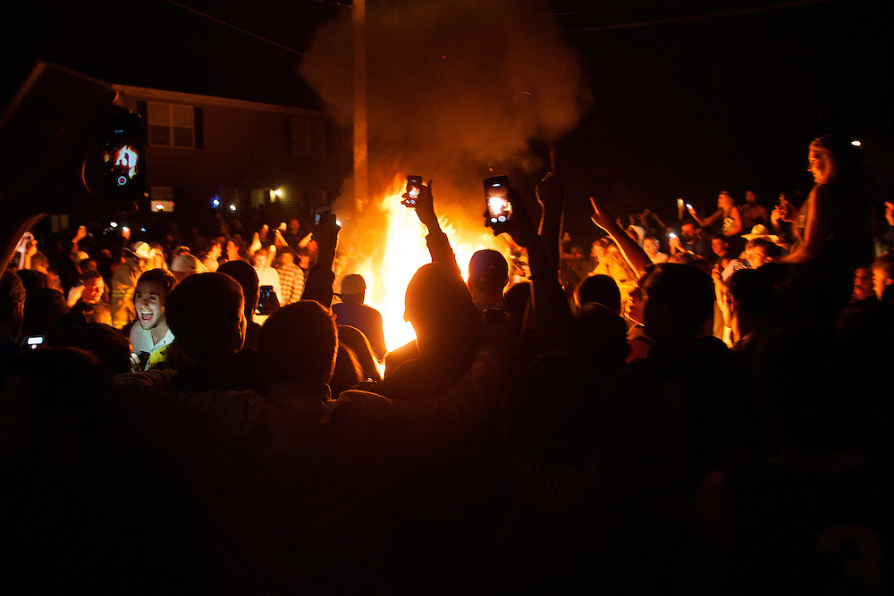 Students on State Street document a fire on their cellphones after Kentucky's win over Louisville in the Sweet 16. The hashtag #StateSt was used more than 4,500 times on Instagram alone during the 4 days of celebrations.