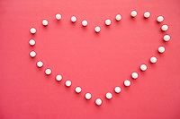 Close-up of push pins forming heart shaped over pink foreground
