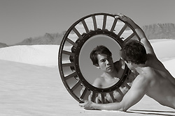Asian American man without a shirt holding a unique mirror in the sand dunes of White Sands, New Mexico