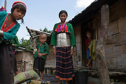 A young girl who is a member of a sub-group of the Palaung ethnic minority stands outside her family's communal house. The tribe is famous for the silver bands un-married girls wear around their waist, the number depending on the wealth of their family. Once they are married most are removed leaving only a few remaining.