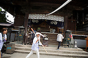 A woman in white clothes and a walking stick in her hand by the first temple at the Shikoku Pilgrimage, 88 temples associated with the Buddhist monk Kūkai (Kōbō Daishi) on the island of Shikoku, Japan.