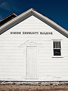 Wisdom Community Building end of white building with boarded-up door and stone foundation.