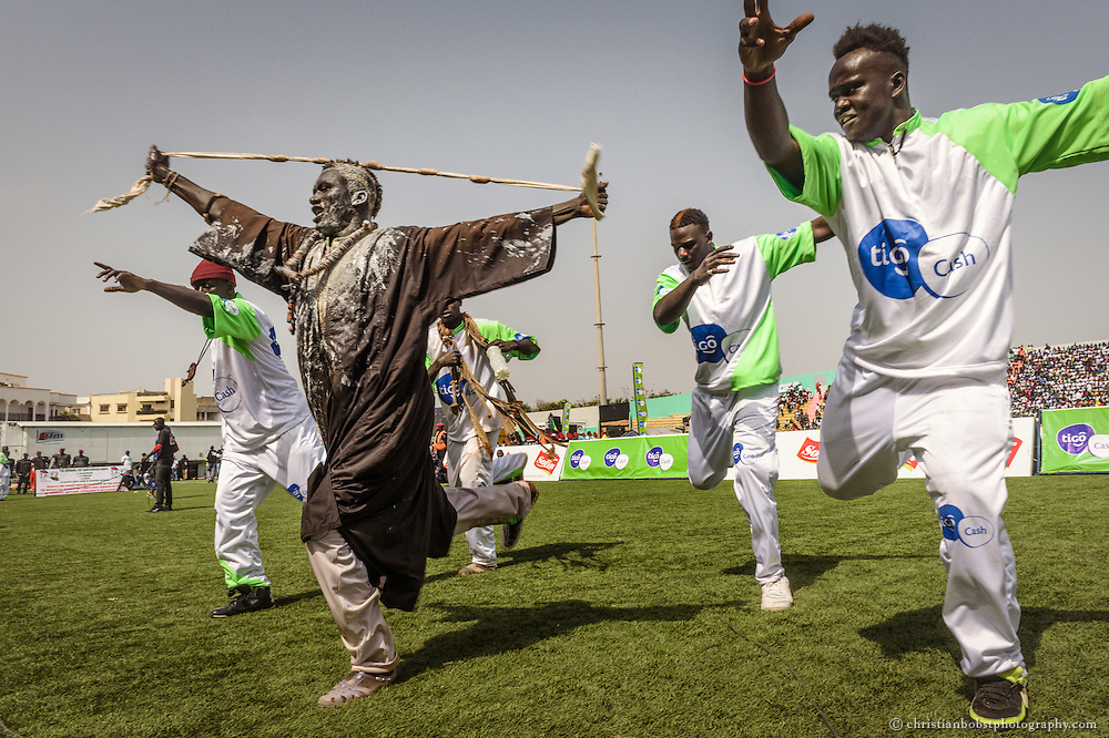 Wrestlers perform a wrestler´s dance    at the Demba Diop stadium in  Dakar, April 5, 2015. The Wrestlers entertain the audience with traditional dances and Gris-gris  ceremonies before their fights. However, the traditional costumes were substituted with high-tech fibre sports clothing and with the logos of modern telecommunication brands.