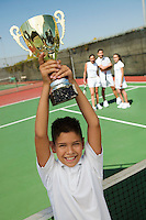 Boy Holding Tennis Trophy at net on tennis court portrait high angle view