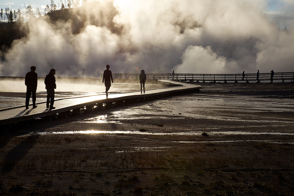Yellowstone National Park's Excelsior Geyser makes a dramatic and moody backdrop to visitors in the early morning light.
