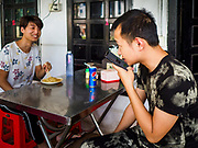 "14 FEBRUARY 2019 - SIHANOUKVILLE, CAMBODIA:  Men who work for Chinese enterprises in Sihanoukville eat lunch in a Chinese noodle shop near their apartment building. There are thousands of Chinese workers in Sihanoukville who work to support the casino and hotel industry in the town. There are about 80 Chinese casinos and resort hotels open in Sihanoukville and dozens more under construction. The casinos are changing the city, once a sleepy port on Southeast Asia's ""backpacker trail"" into a booming city. The change is coming with a cost though. Many Cambodian residents of Sihanoukville  have lost their homes to make way for the casinos and the jobs are going to Chinese workers, brought in to build casinos and work in the casinos.      PHOTO BY JACK KURTZ"