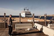 Lampedusa, Italia - Un lampedusano attende l'attracco della nave nel porto dell'isola. Non di rado capita che la nave, a causa del mare mosso, non raggiunga Lampedusa per giorni. Questo comporta un numero considervole di disagi: dai carri funebri che trasportano isolani deceduti lontano da Lampedusa costretti ad attendere a porto Empedocle  ai beni di prima necessit&agrave;.<br /> Ph. Roberto Salomone