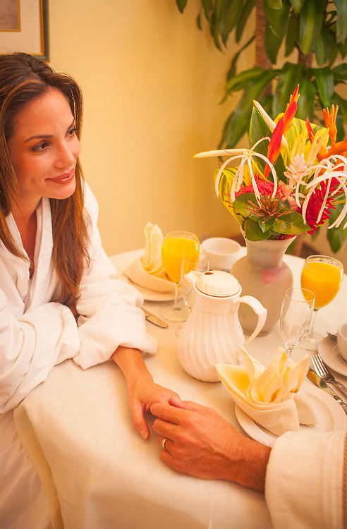 A couple hold hands on the breakfast table in their room at The Fisher Island Club and Resort