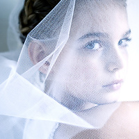 Young girl looking at camera dressed in white with veil over her face
