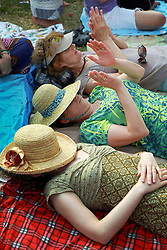 26 April 2014. New Orleans, Louisiana.<br /> Ladies in hats applaud the band on stage at the New Orleans Jazz and Heritage Festival. <br /> Photo; Charlie Varley/varleypix.com