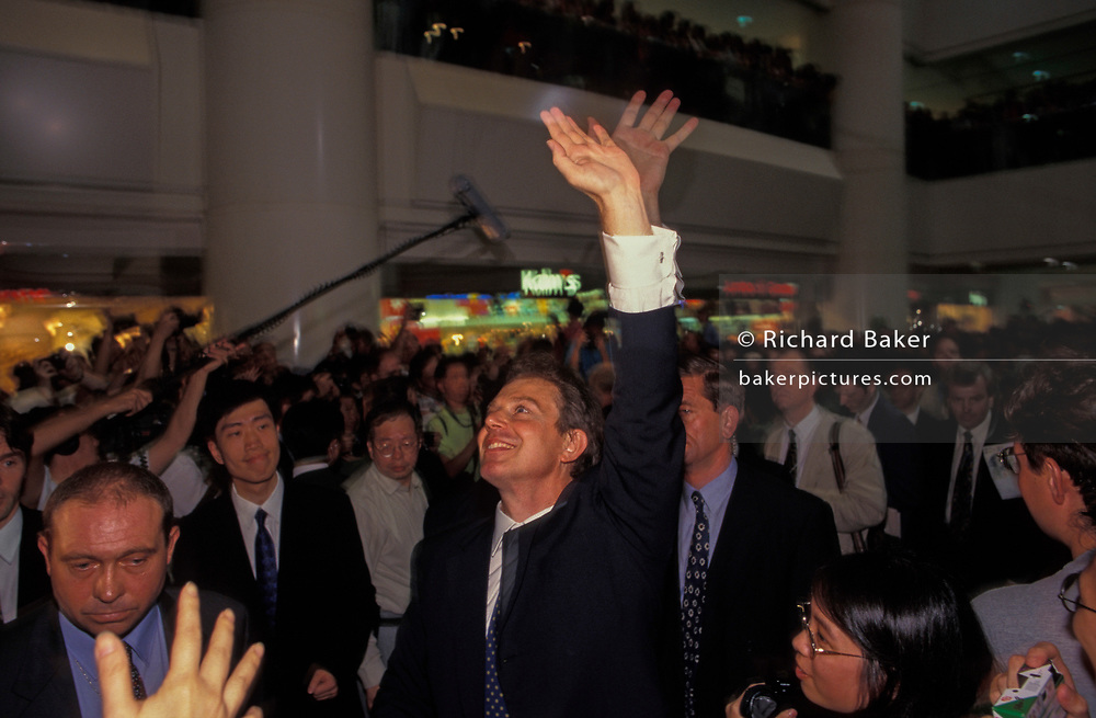 British Prime Minister Tony Blair greets crowds in the Pacific shopping mall on the eve of the handover of sovereignty from Britain to China, on 30th June 1997, in Hong Kong, China. Blair accompanied the outgoing Governor, Chris Patten on the walkabout around parts of the still-British colony. Midnight signified the end of British rule, and the transfer of legal and financial authority back to China. Hong Kong was once known as 'fragrant harbour' (or Heung Keung) because of the smell of transported sandal wood.