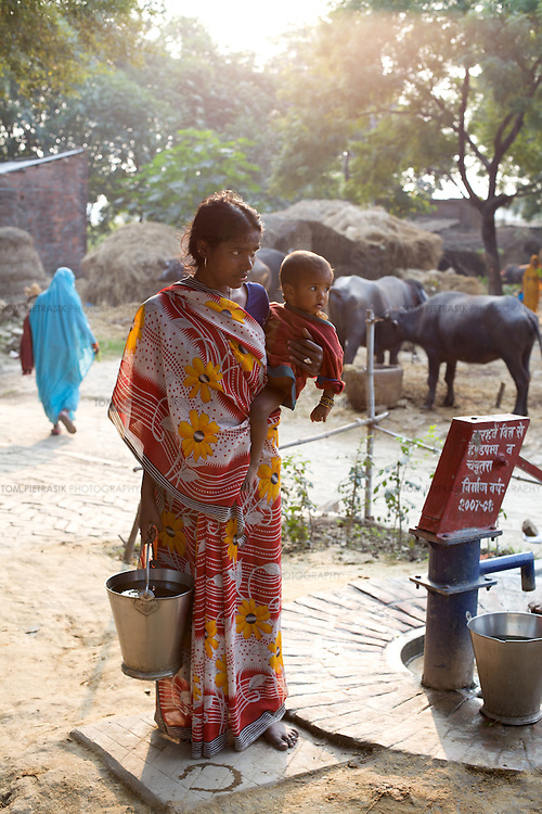 A woman and her child at a hand pump in Thathara village. In Thathara village, 80 percent of households are connected to a network of drains for the disposal of waste water. This reduces the incidence of stagnant water. UNICEF trained masons in the construction of this network of drains. ..UNICEF and the Uttar Pradesh Government, have identified 100 model Gram Panchayats (local-level village administration) in Varanasi District (out of a total of 702). The promotion of good sanitation and hygiene practices in these Gram Panchayats allows them to serve as examples for the remaining areas of the district to emulate. The promotion of hygiene and sanitation includes the construction and painting of school toilet blocks, the construction of individual toilets in households, the digging of garbage pits, recycling waste water and encouraging personal hygiene awareness. ..Only 32 percent of those living in Uttar Pradesh, India's largest state, have access to a toilet. Uttar Pradesh faces many challenges in it's efforts to address this deficiency. UNICEF supports the Uttar Pradesh government's sanitation and hygiene project at both the state and district levels. UNICEF is working to increase the capacity of all of those involved in the sanitation and hygiene project from state-level administrators through to Panchayati Raj (local-level administration) officers and influential individuals, including teachers, who live among rural communities. UNICEF has prioritised the need to communicate the importance of good sanitation and hygiene practice to these communities. The Uttar Pradesh government and UNICEF have focussed their campaign on eight districts (including Varanasi) with the intention that these serve as models for the remaining 62 districts of the state. UNICEF have identified areas of shortcoming within the government program and proposed solutions. These solutions include the proper training of masons, the provision of rural pans (toilet bowls which require less water