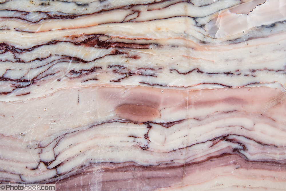 Bands of pink and white layers demark the 1.19-billion-year-old Bass limestone of the Grand Canyon Supergroup, on the fascinating Trail of Time interpretive exhibit on the South Rim of Grand Canyon National Park, Arizona, USA. Starting west of Yavapai Geology Museum, walk for 1.3 miles on the paved trail backward in time from today toward the oldest rock in Grand Canyon, Elves Chasm gneiss, 1.840 billion years old. Or begin east of Verkamp's Visitor Center, walking forward in time toward the youngest rock in the Grand Canyon, Kaibab Limestone, 270 million years old. Starting at least 5 to 17 million years ago, erosion by the Colorado River has exposed a column of distinctive rock layers, which date back nearly two billion years at the base of Grand Canyon. While the Colorado Plateau was uplifted by tectonic forces, the Colorado River and tributaries carved Grand Canyon 6000 feet deep, 277 miles  long and up to 18 miles wide.