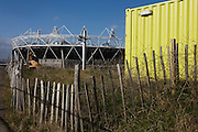 Incongruous landscape of bygone era fencing, shipping container and new 2012 Olympic stadium on Stratford Greenway